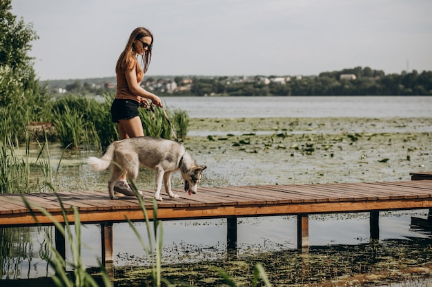 Giovane donna con il suo cane husky sul lago