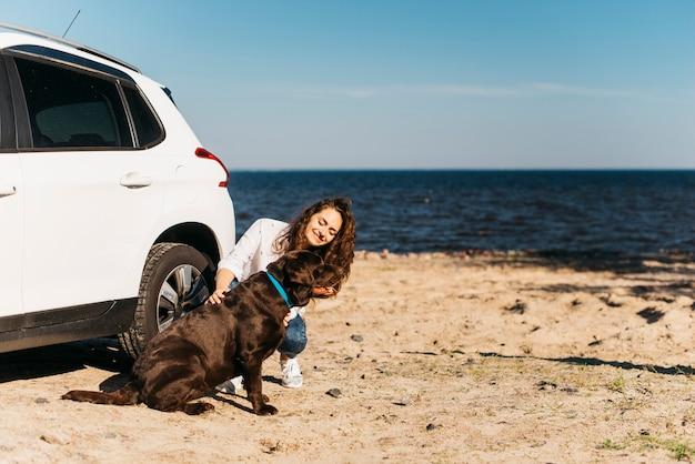 Giovane donna con il suo cane in spiaggia