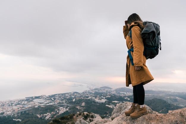 Giovane donna con il suo zaino in piedi sulla cima della montagna guardando vista idilliaca