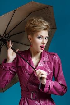 Giovane donna con l'ombrello sull'azzurro