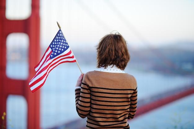 Giovane donna con la bandiera americana che considera golden gate bridge famoso a san francisco, california, usa