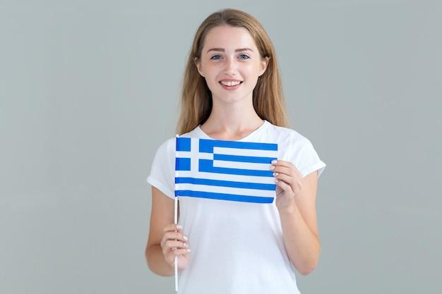 Giovane donna con la bandiera della grecia in mano isolato su grigio