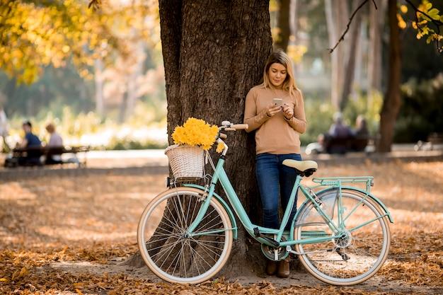 Giovane donna con la bicicletta che utilizza smartphone nel parco di autunno