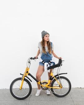Giovane donna con la bicicletta in piedi sul marciapiede