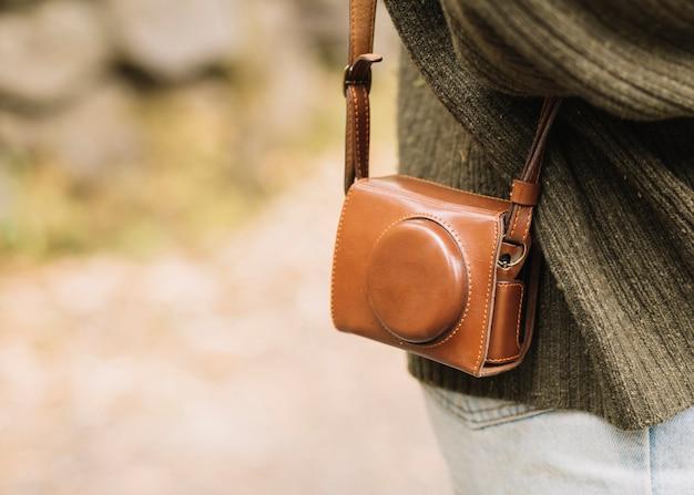 Giovane donna con la borsa della macchina fotografica in natura