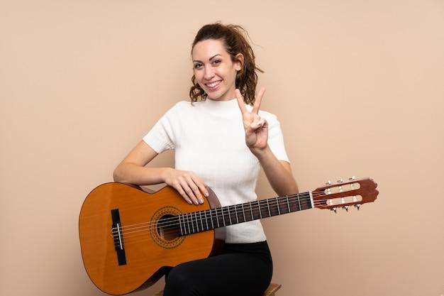Giovane donna con la chitarra che sorride e che mostra il segno di vittoria
