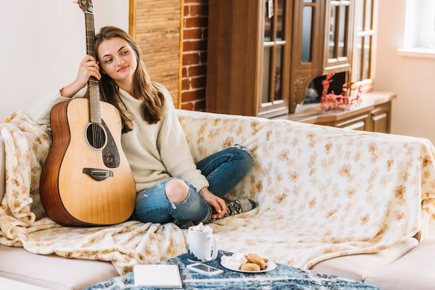 Giovane donna con la chitarra vicino tavolo con smartphone, blocco note, tazza di bevanda e biscotti