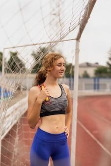 Giovane donna con la corda che si siede al cancello footbal