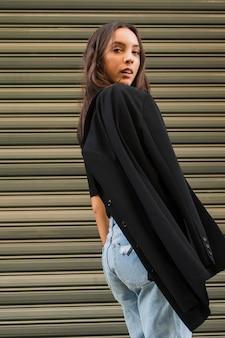 Giovane donna con la giacca sulla spalla in piedi davanti all'otturatore di ferro