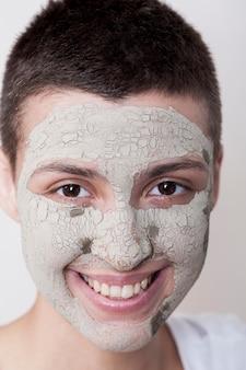 Giovane donna con la maschera che esamina il primo piano della macchina fotografica