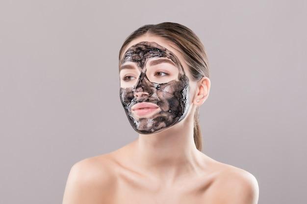Giovane donna con la maschera nera purificante sul suo fronte isolato sulla parete bianca