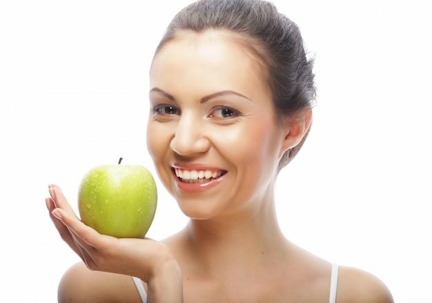 Giovane donna con la mela verde isolata su bianco