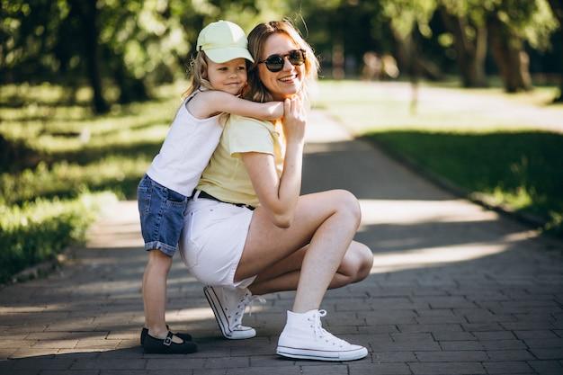Giovane donna con la piccola figlia che cammina nel parco