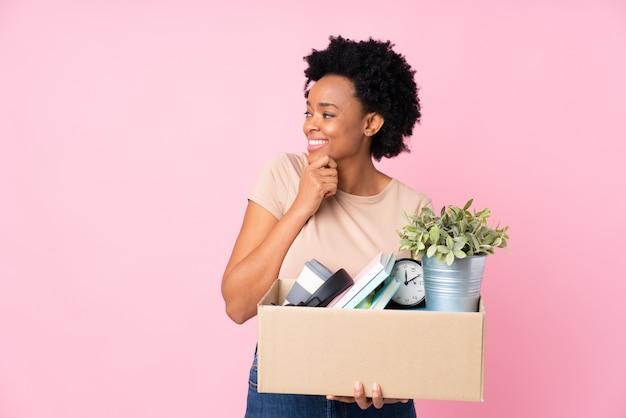 Giovane donna con la scatola piena di cose sopra la parete isolata