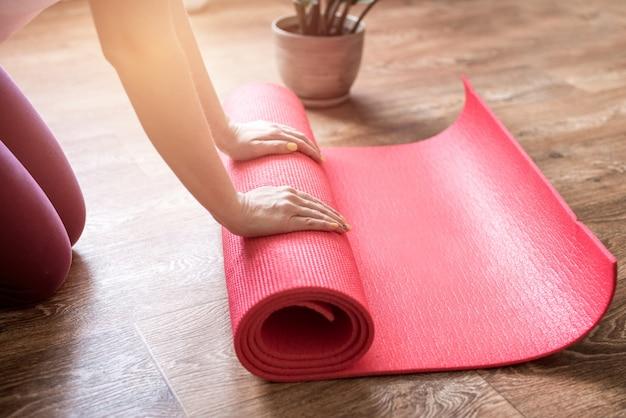 Giovane donna con la stuoia di yoga all'interno, forma fisica sana e concetto di sport. donna che rotola la sua stuoia di yoga dopo un allenamento.