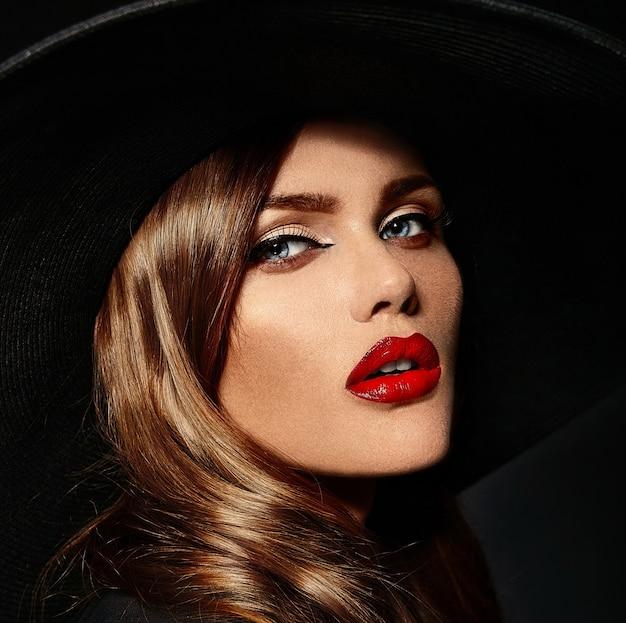 Giovane donna con labbra rosse e cappello nero