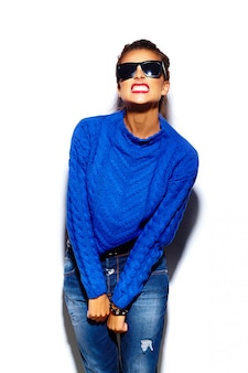 Giovane donna con labbra rosse e maglione blu in occhiali da sole
