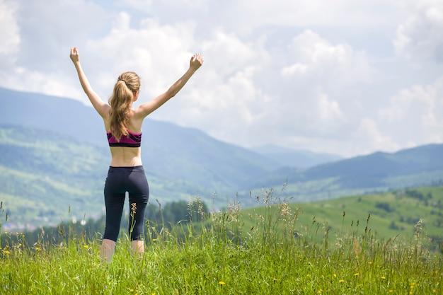 Giovane donna con le braccia alzate all'aperto