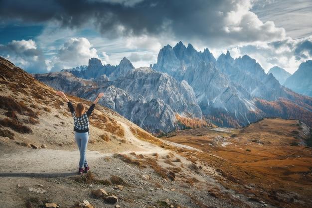 Giovane donna con le braccia alzate e maestose montagne al tramonto in autunno