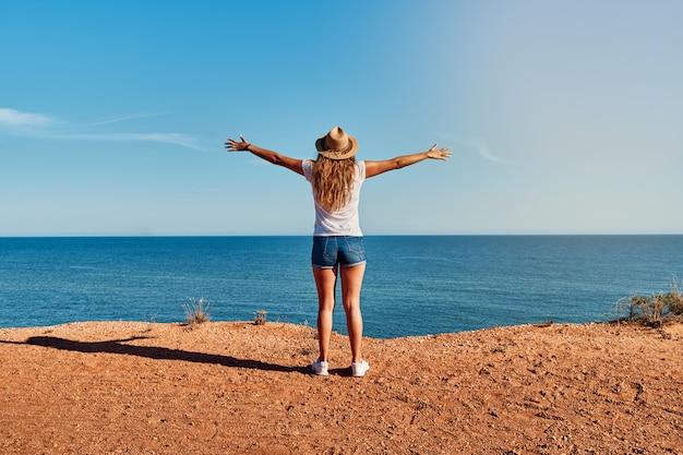 Giovane donna con le braccia aperte e il cappello di fronte al mare in estate