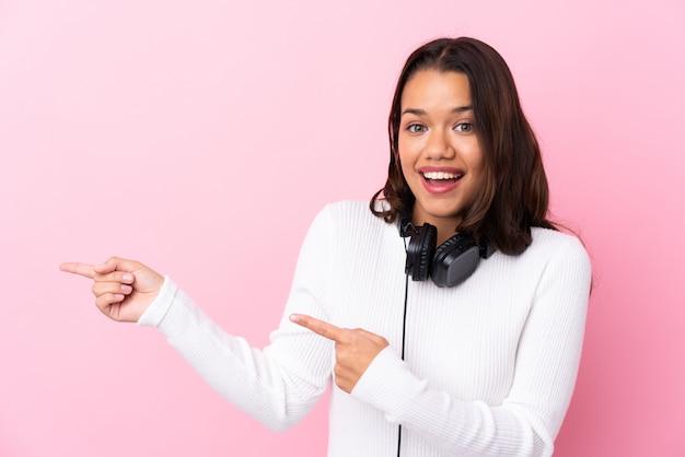 Giovane donna con le cuffie sopra il muro rosa sorpreso e indicando il lato