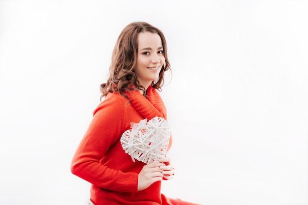Giovane donna con le parentesi graffe che tengono un cuore