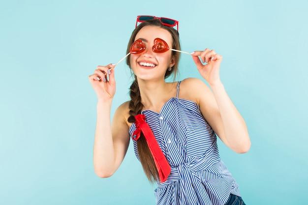 Giovane donna con lecca-lecca a forma di cuore