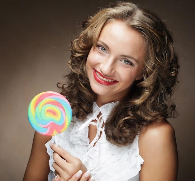 Giovane donna con lecca-lecca colorata