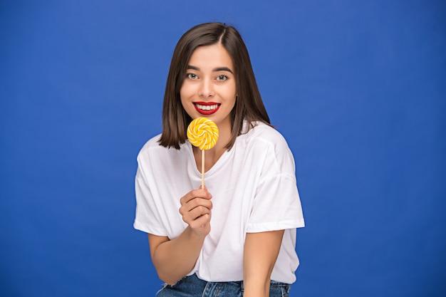 Giovane donna con lecca-lecca colorato