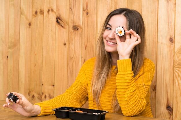 Giovane donna con legno di sushi