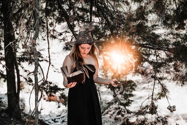 Giovane donna con libro e candela guardando nella foresta