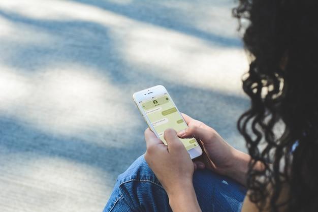 Giovane donna con lo smartphone che invia messaggio di testo