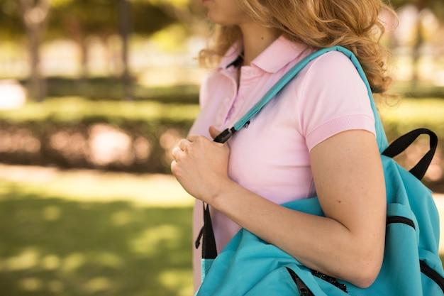 Giovane donna con lo zaino nel parco