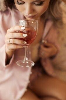 Giovane donna con lunghi capelli biondi platino in pigiama di seta rosa seduto in una poltrona con bicchiere di vino e bere. concetto di spose mattina prima del matrimonio