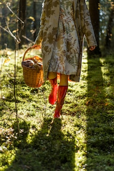 Giovane donna con lunghi capelli rossi in un vestito di lino raccolta funghi nella foresta