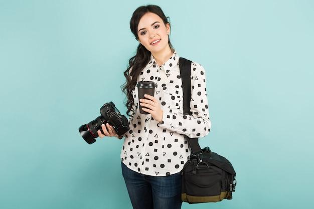 Giovane donna con macchina fotografica e caffè