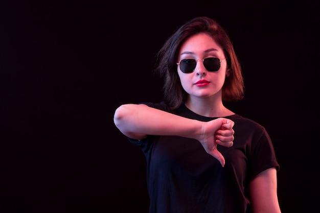 Giovane donna con maglietta nera con il pollice verso il basso