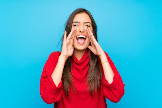Giovane donna con maglione rosso che grida con la bocca spalancata