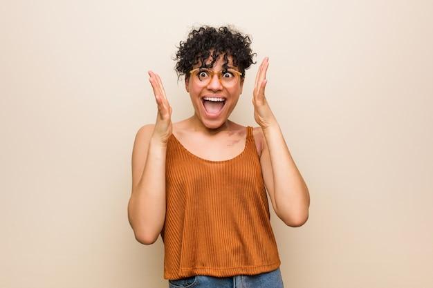 Giovane donna con marchio di nascita in pelle che celebra una vittoria o un successo, è sorpreso e scioccato