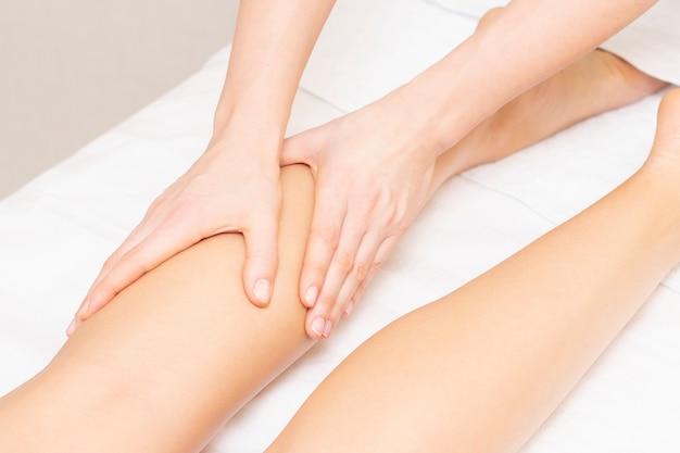 Giovane donna con massaggio ai piedi nel salone di bellezza