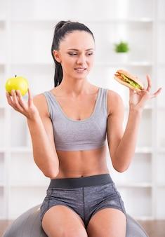 Giovane donna con mela e hot dog dopo aver esercitato a casa.