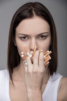 Giovane donna con molte sigarette in bocca.