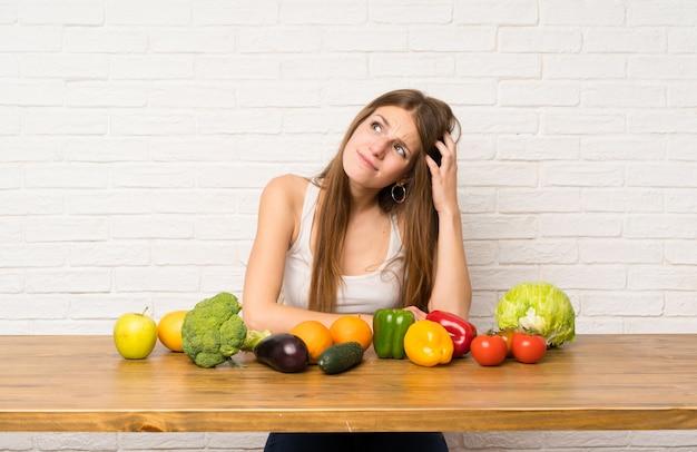 Giovane donna con molte verdure che hanno dubbi e con espressione del viso confuso
