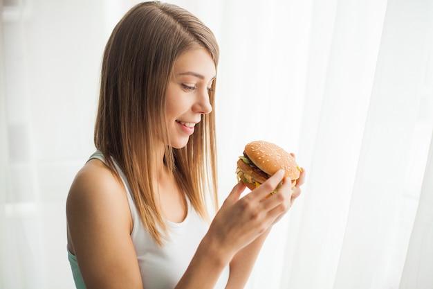 Giovane donna con nastro adesivo sulla bocca, impedendole di mangiare cibo spazzatura, concetto di cibo sano