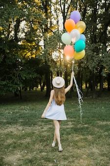 Giovane donna con palloncini all'aperto