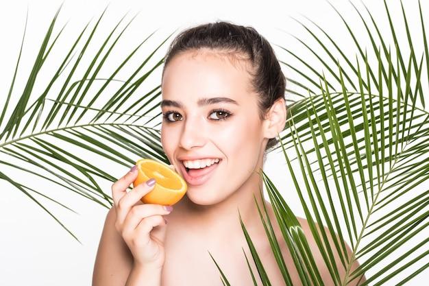 Giovane donna con pelle perfetta tenendo gli agrumi in mano, circondato da foglie di palme isolate sul muro bianco