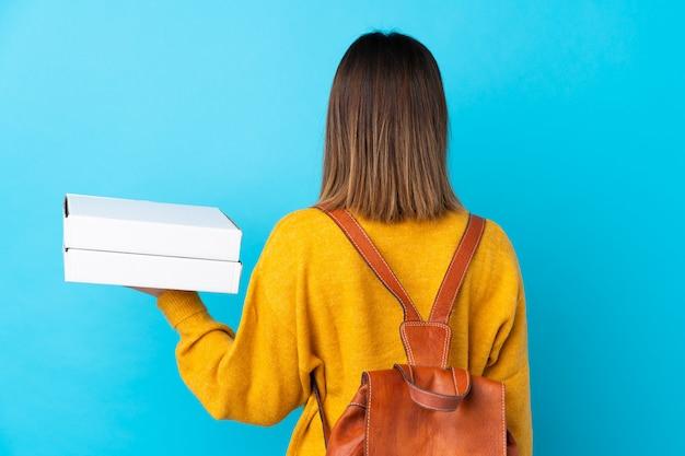 Giovane donna con pizze sul muro blu