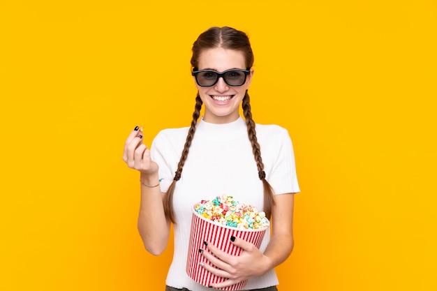 Giovane donna con popcorn sopra la parete isolata