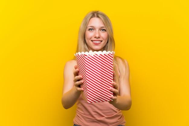 Giovane donna con popcorn sul muro rosa