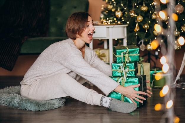 Giovane donna con regalo di natale dall'albero di natale